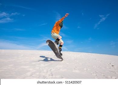 Snowboarder, wearing a scarf to protect against sand, is jumping on a sand dune. Sand boarding in desert. Low point shooting. Wide angle.