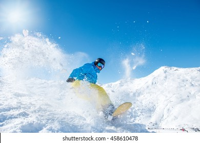 Snowboarder in winter sports gear riding down the slope at a ski resort