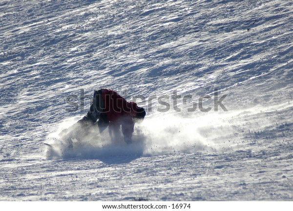 Snowboarder wiping out in the snow.