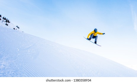 Snowboarder with yellow jacket jumping off a slope