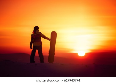 Snowboarders female silhouette with snowboard on sunset backdrop. Space for text. Snowboarding or skiing concept