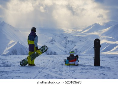 Snowboarders have a rest and look at the winter mountains landscape.