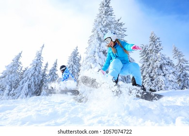 Snowboarders on ski piste at snowy resort. Winter vacation