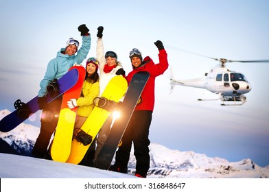 Snowboarders on Top of the Mountain with Heli Ski Concept