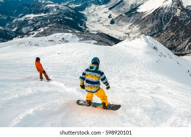 snowboarders is riding down with snowboards from powder snow hill or mountain