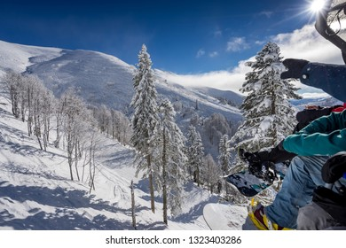 Snowboarders sitting on ropeway, point to the beautiful landscape and ski slopes in the winter resort of Krasnaya Polyana