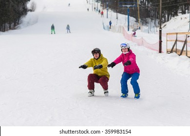 Snowboarders and skiers do warm up before exercise. Athletes crouch on the slope in winter.
