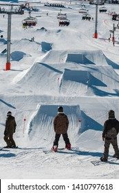 Snowboarders waiting for their turn in front of the kickers in the snowpark