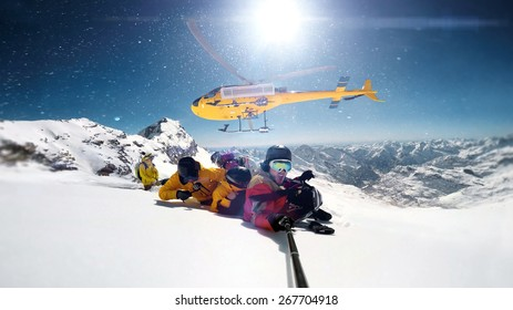 snowboarders were dropped by a helicopter at the top of the mountains while one person is taking a smile selfie with a wide angle camera.  The sun is shining brightly in the blue sky.