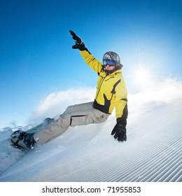 Snowboarding man at flattened piste - slope