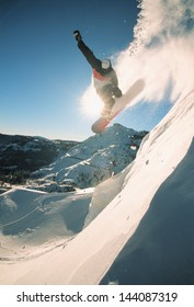 Snowboarding off a cliff off piste on a sunny day in Donner Pass, California, USA