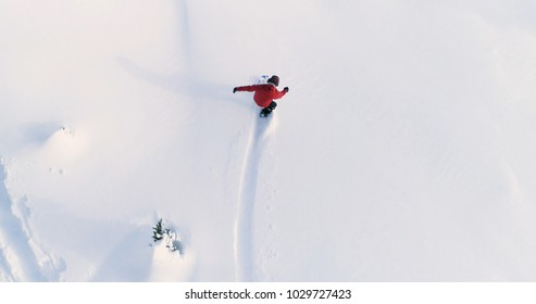 Snowboarding Overhead Top Down View of Snowboarder Riding Through Fresh Powder Snow Down Ski Resort or Backcountry Slope - WInter Extreme Sports Background