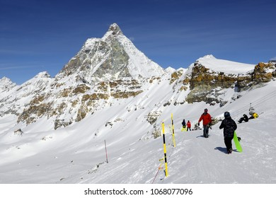 Snowborders under Matterhorn peak - Monte Cervino, Italy. Mountain situated on the border between Switzerland and Italy, over the Swiss Zermatt and the Italian town of Breuil-Cervinia