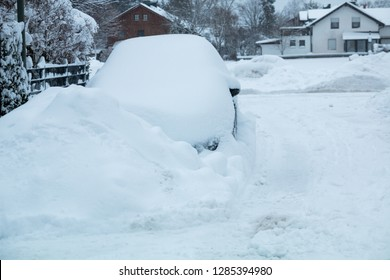 snowbound  passenger car, parked  in the street, with thick snow cover and heap of snow