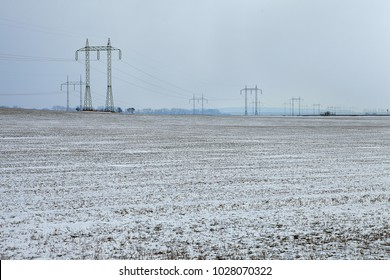 Snow-bound wind-swept tillage with power towers in bg. Snowy field with transmission towers in the background. Outfield under snow. Windswept ground. Snow-covered arable land. Windburned snowy ager.