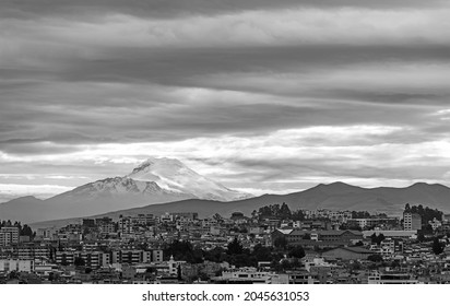 Snowcapped Cayambe volcano with Quito city in black and white, Ecuador.