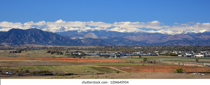 the snow-capped front range of the colorado rocky  mountains on a sunny fall day with a pumpkin patch in the foreground, as seen from broomfield, colorado