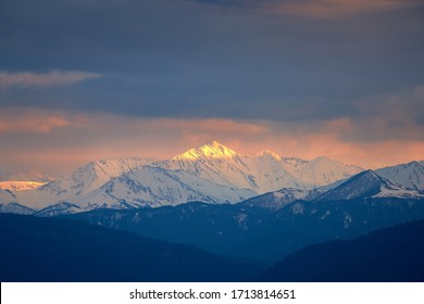 Snow-capped mountain in the sunset light under a stormy sky. Mount Tybga, North Caucasus. Russia.