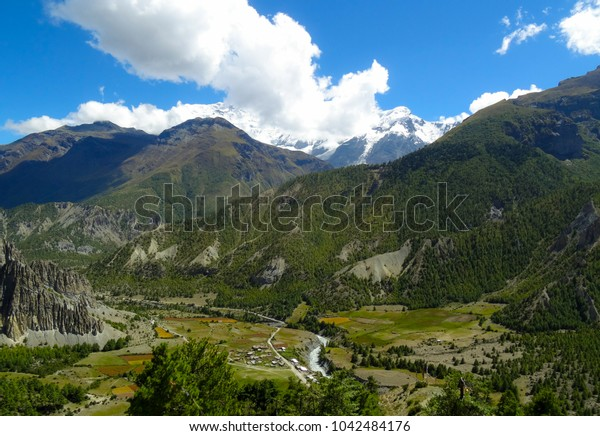 snow-capped mountains behind a green mountain