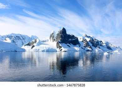 Snow-capped mountains and icy coasts at the entrance to the Lemaire Channel in the Antarctic Peninsula, Antarctica