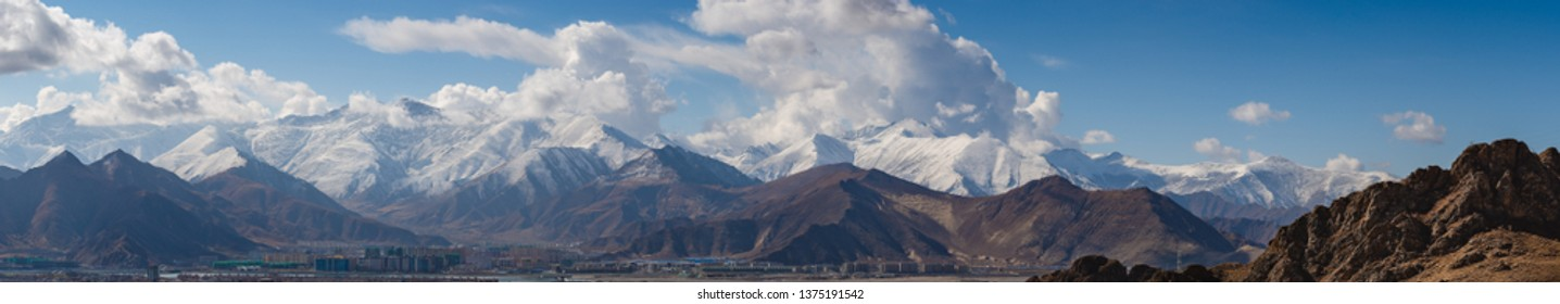 Snow-capped mountains loom over the city of Lhasa in Tibet, China.