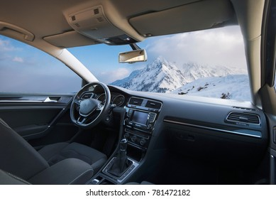 snow-capped mountains seen from inside a car