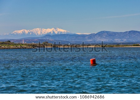 Snow-capped Pyrenees mountains seen from a boat leaving the channel at Gruissan in Southern France