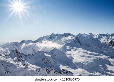 Snowcapped summits of the Alps with backlight.