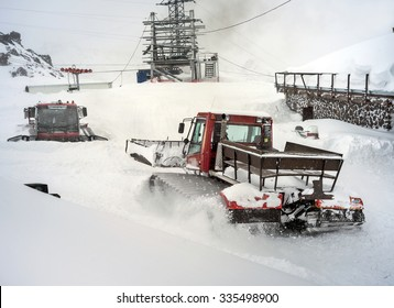 Snowcat in motion in snowfall on slope in the mountains at skiing resort Elbrus, preparing and clearing the track