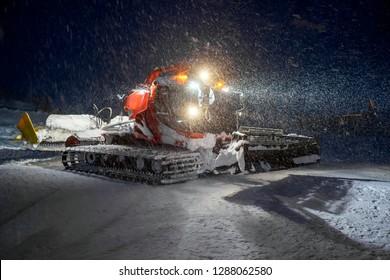 Snowcat preparing a slope at night in high mountains at skiing resort of the North Caucasus Elbrus