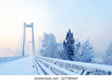 snow-covered bridge over the river in the winter in the fog,