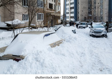 Snow-covered car on a city street. Driver digs car out of a snowdrift after a snowstorm.