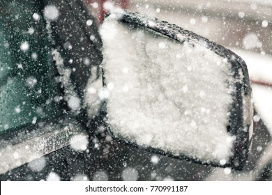 Snow-covered car rear view mirrors