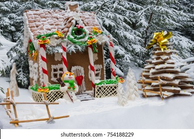 Snow-covered homemade gingerbread house, gingerbread Christmas tree and a sugar mastic snowman on forest background. Mockup for seasonal offers and holiday post card