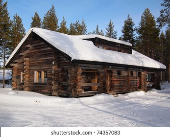 Snow-covered log cabin in a holiday resort in Yllas, Lapland, Finland.