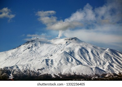 Snow-covered Mount Etna Volcano smoking in winter -  view from Giardini Naxos, Sicily