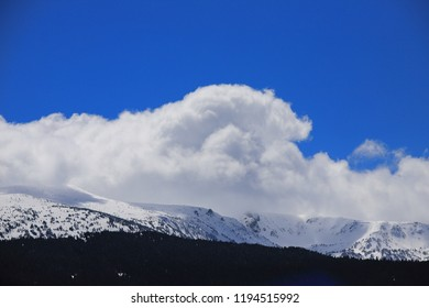 Snow-covered mountain in the Pyrenees covered with cumulus clouds, Aude in the southern France