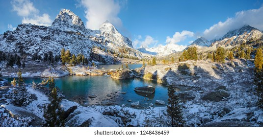 Snow-covered mountain slopes along the shores of a picturesque lake, early winter, panorama landscape
