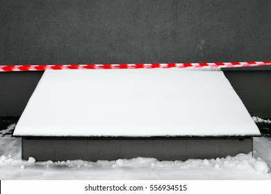 A snow-covered overhang with a stretched red and white ribbon on the background of a gray wall. Russia, Moscow, November 2016.