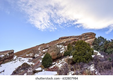 Snow-covered red rock stone against blue cloud strewn sky, Red Rocks Park and Amphitheatre, Morrison County, Colorado, USA