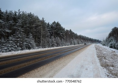 Snow-covered road. The forest in the background.