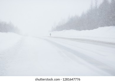 Snow-covered road and a lonely man. Snowfall and large snowdrifts on the forest background. Cold and snowy winter weather. Kolyma Highway, Magadan Region, Far East of Russia. Perfect for background.