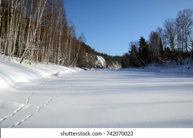 Snow-covered rocks on the shore of icy river and traces of wild animals in the snow. Chusovaya river, Ural, Russia.