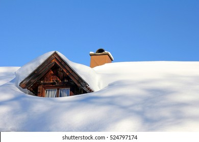 A snow-covered roof of a wooden house