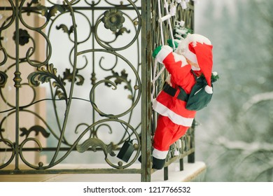 Snow-covered Santa climbs the balcony on the rope ladder. Christmas installation