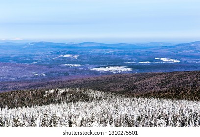 Snow-covered trees on Mount Kachkanar. The view from the height of the winter forest and mountains