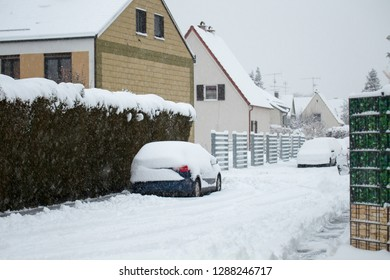 snow-covered vehicle on a street in winter with a thick blanket of snow