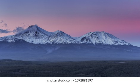 snow-covered volcanoes in pink light close-up In the foreground is a small lake and a dark green forest. Kamchatka volcanoes.Panoramic view.Nature of Kamchatka.Petropavlovsk-Kamchatka region.