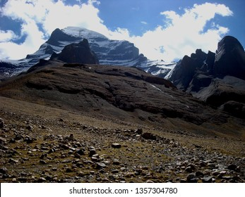 The snow-covered Western wall of Kailash in Tibet, the rock monolith, in the foreground, placers of stones and rock monolith