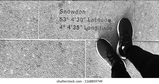 Snowdon, Snowdonia, Wales, UK Aug 2017. Nike trainers standing at top of mountain with Longitude and latitude locator.